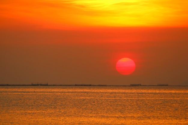 Zachód słońca z powrotem wieczorem ciemnopomarańczowa chmura na niebie nad morzem