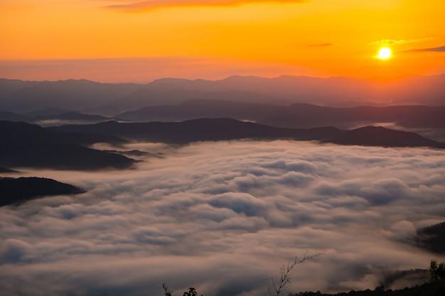 Zachód słońca z widokiem na góry z mgłą