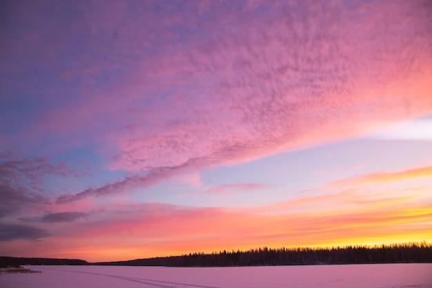 Zachód słońca zimowy krajobraz z zaśnieżoną drogą w kolorach fioletu i różu