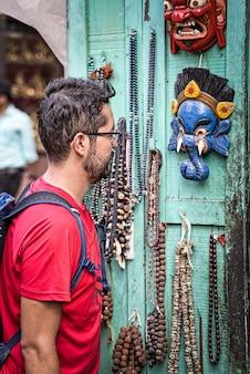 Zachodni chłopiec o azjatyckich rysach, krótkiej czarnej brodzie i okularach, patrząc na maski i pamiątki wiszące na turkusowych drewnianych drzwiach w sklepie w nepalu w azji. zdjęcie pionowe