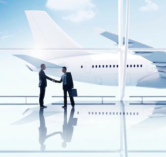 Zachodni i azjatykci biznesmena uścisku dłoni spotkania lotnisko