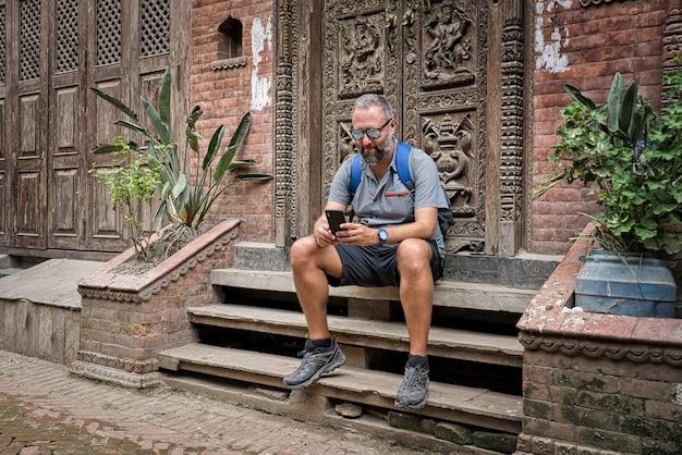 Zachodni turysta w szarych szortach, lustrzanych okularach przeciwsłonecznych i niebieskiej koszuli siedzący na ulicy obok rzeźbionych drewnianych drzwi w nepalu sprawdza smartfona. koncepcja stylu życia, podróży i technologii