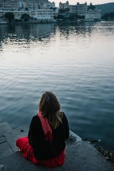 Zachodnia kobieta cieszy się widok taj jezioro w udaipur