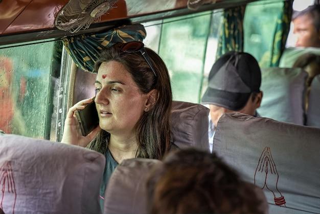 Zachodnia kobieta z czerwoną kropką indu na czole (bindi) w lokalnym autobusie w katmandu rozmawia przez telefon