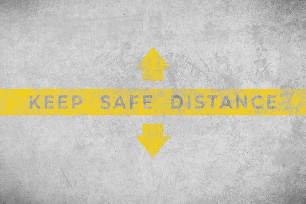Zachowaj bezpieczną odległość. tekst malowany na postarzanej betonowej podłodze. ludzie czekają na swoją kolej z rzędu