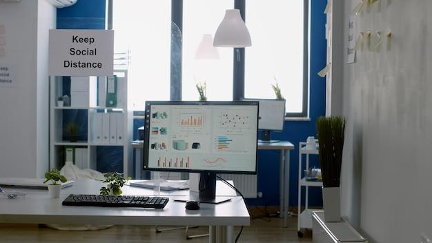Zachowaj plakat odległości społecznej na plastikowym separatorze w pustym nowoczesnym biurze, bez nikogo w nim podczas globalnej epidemii koronawirusa covid 19. przestrzeń biznesowa do pracy