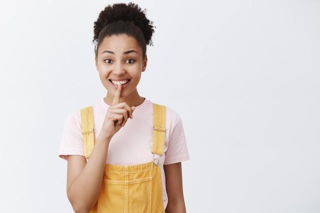 Zachowaj tajemnice. portret uroczej, sympatycznej, uroczej afroamerykanki w żółtym modnym kombinezonie, mówiącej cii, pokazując gest uciszenia, uśmiechając się i trzymając palec wskazujący na ustach