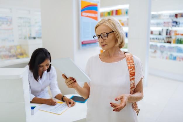 Zachowaj uwagę. uważna dojrzała kobieta w okularach podczas wizyty w aptece