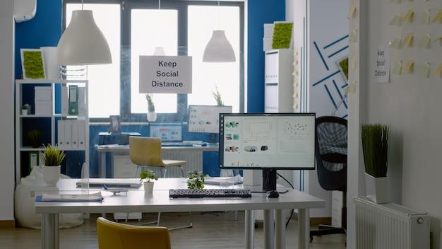 Zachowaj znak odległości społecznej w pustym biurze firmy bez nikogo w nim. praca korporacyjna podczas globalnej pandemii z pomiarem bezpieczeństwa przeciwko covid 19
