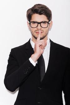 Zachowanie tajemnicy biznesowej. poważny młody człowiek w formalwear, trzymający palec na ustach i patrzący na kamerę, stojąc na białym tle
