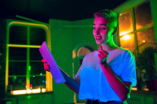 Zachwycający. kinowy portret stylowej kobiety w oświetlonym neonem wnętrzu. stonowane jak efekty kinowe, jasne neonowane kolory. model kaukaski za pomocą tabletu w kolorowych światłach w pomieszczeniu. kultura młodzieżowa.