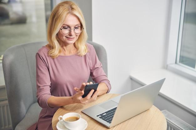 Zachwycona biznesowa dama z uśmiechem na twarzy siedząc przy stole w kawiarni