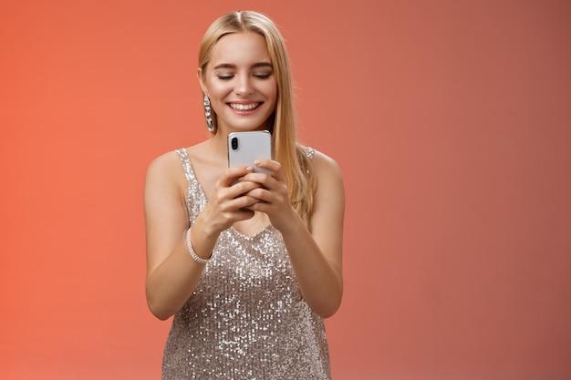 Zachwycona delikatna blond kobieta glamour w srebrnej stylowej błyszczącej sukni kolczyki brilliand trzymając smartfon robi zdjęcie przyjacielowi uchwycić moment celebracji klubu nocnego, czerwone tło uśmiechnięte.