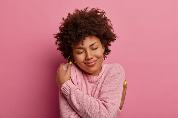 Zachwycona delikatna kobieta o kręconych włosach, obejmuje się, przytula własne ciało