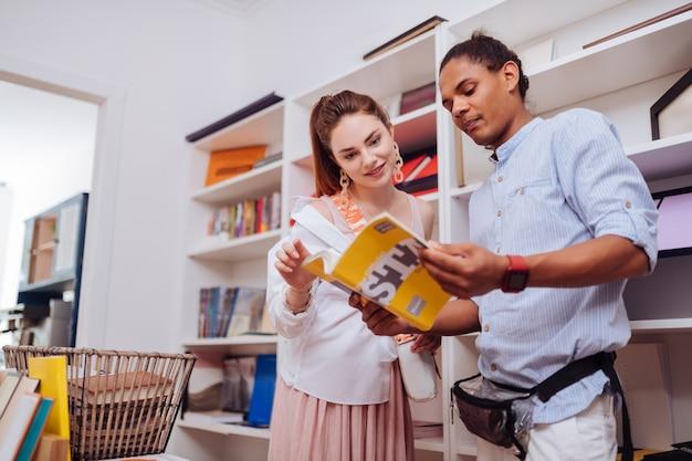 Zachwycona długowłosa dziewczyna z uśmiechem na twarzy stojąc obok sprzedawcy