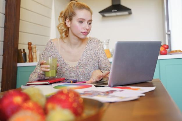 Zachwycona dziewczyna siedząca przy stole podczas pracy nad swoim projektem