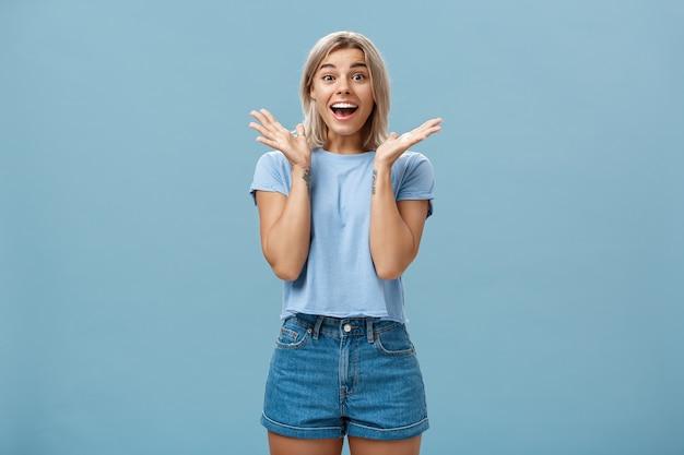 Zachwycona, entuzjastyczna, szczęśliwa kobieta w modnej koszulce i szortach, klaszcząca w dłonie ze zdumienia, szeroko uśmiechnięta, zaskoczona i radosna