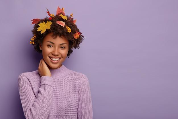 Zachwycona etniczna dziewczyna wyraża szczere emocje, dotyka szyi i radośnie chichocze, ubrana w ciepły sweter z dzianiny, patrzy z szerokim uśmiechem, ma fryzurę w żółte listki