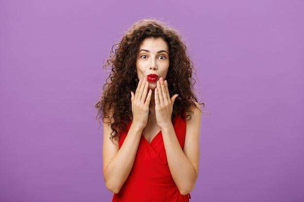 Zachwycona i podekscytowana luksusowa dorosła kobieta z kręconymi włosami z wieczorowym makijażem w czerwonej sukience składanymi ustami w zdumieniu trzymając dłonie na twarzy uważnie słuchając ciekawej plotki o fioletowej ścianie.