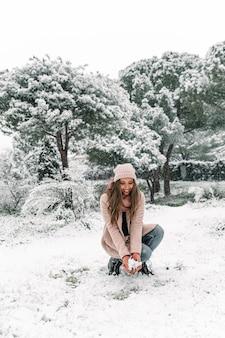 Zachwycona kobieta w ciepłych ubraniach siedzi w lesie ze stosem śniegu i ciesząc się weekendem w zimie