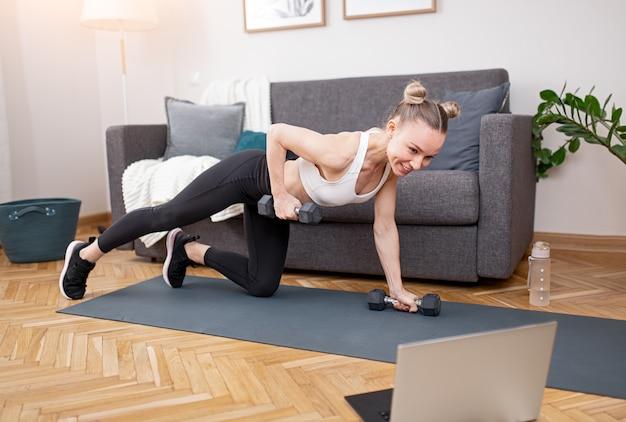 Zachwycona lekkoatletka uśmiecha się i robi ćwiczenia z hantlami w pobliżu laptopa podczas treningu online w domu
