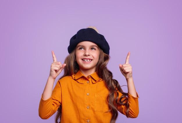 Zachwycona mała dziewczynka w swobodnej pomarańczowej koszuli i berecie, uśmiechnięta i skierowana w górę
