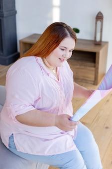 Zachwycona miła kobieta siedząca na łóżku czytająca ciekawy artykuł