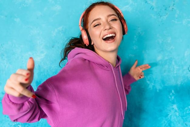 Zachwycona miła kobieta w słuchawkach słuchająca muzyki i tańcząca na białym tle nad niebieską ścianą w pomieszczeniu