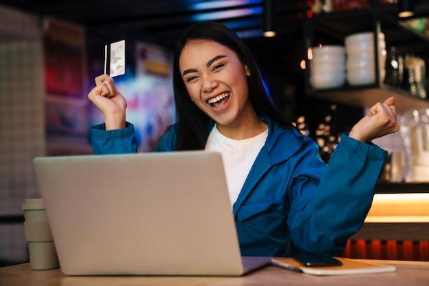 Zachwycona młoda azjatycka kobieta pracująca z laptopem i trzymająca kartę kredytową siedząc w kawiarni