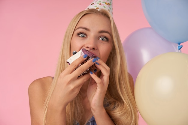Zachwycona młoda blondynka raduje się jedząc tort urodzinowy, radośnie patrząc w kamerę z szeroko otwartymi oczami, ciesząc się miłą imprezą razem z przyjaciółmi, pozując na różowym tle