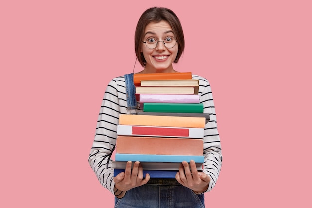 Zachwycona młoda kobieta nosi stos podręczników, szeroko się uśmiecha, poznaje przydatne informacje z encyklopedii, ma ciemne włosy