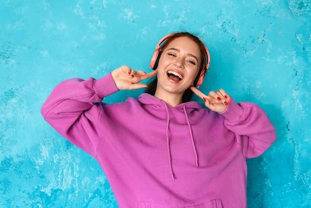 Zachwycona młoda kobieta w słuchawkach słuchająca muzyki i tańcząca na białym tle nad niebieską ścianą w pomieszczeniu
