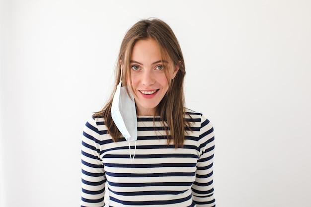Zachwycona młoda kobieta w swobodnej koszuli w paski z maską ochronną wiszącą na uchu patrząc na kamery