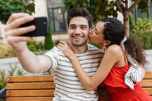 Zachwycona młoda para robi sobie zdjęcie selfie na telefonie komórkowym i całuje się siedząc na ławce na zielonej ulicy
