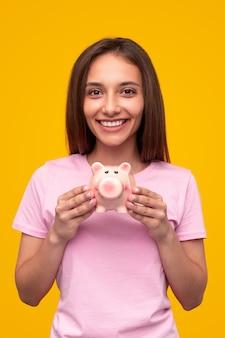 Zachwycona młoda studentka w swobodnym stroju pokazująca skarbonkę, jednocześnie oszczędzając pieniądze na przyszłość