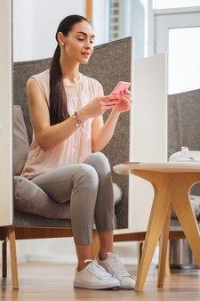 Zachwycona pozytywna kobieta korzystająca ze swojego smartfona w oczekiwaniu na wizytę w salonie kosmetycznym