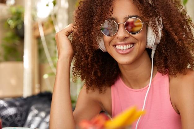 Zachwycona pozytywna kobieta w modnych okrągłych okularach przeciwsłonecznych