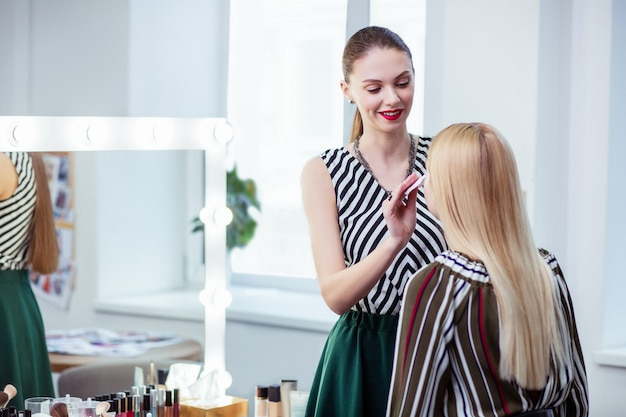 Zachwycona pozytywna wizażystka patrząca na swojego klienta podczas wykonywania swojej ulubionej pracy