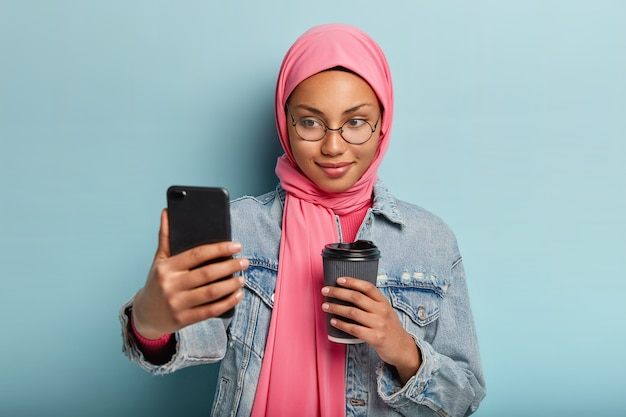 Zachwycona, przyjemnie wyglądająca muzułmańska dziewczyna pije kawę na wynos, robi selfie lub prowadzi rozmowę wideo, ubrana w stylową dżinsową kurtkę i hidżab, udostępnia zdjęcia obserwującym w sieciach społecznościowych