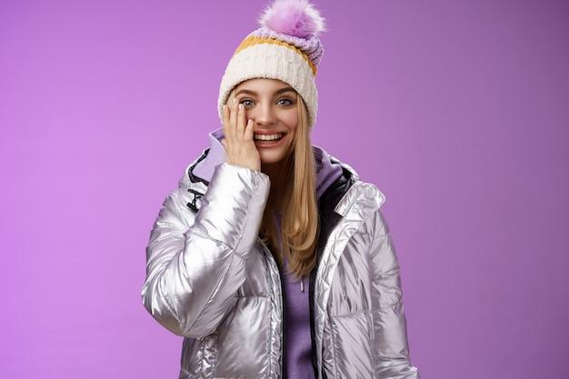 Zachwycona rozbawiona delikatna blond dziewczyna wygłupia się wyglądając figlarnie grając w śnieżki dotknąć policzka zdziwiona czuć spełnienie marzeń ciesząc się wakacjami, zimą, chłopakiem, stojącym na fioletowym tle.