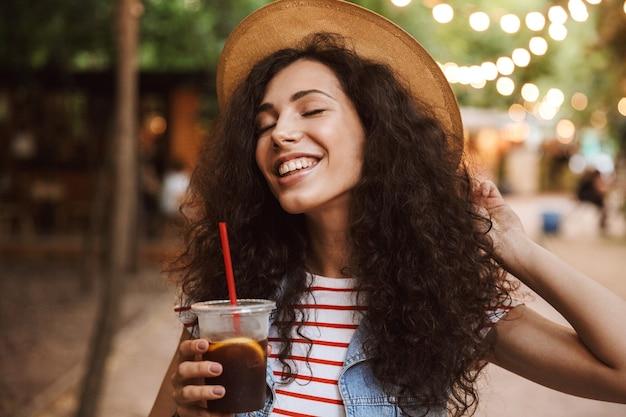 Zachwycona śliczna kobieta ubrana w letni słomkowy kapelusz pijący zimną herbatę z plastikowego kubka, spacerując po parku z kolorowymi lampami