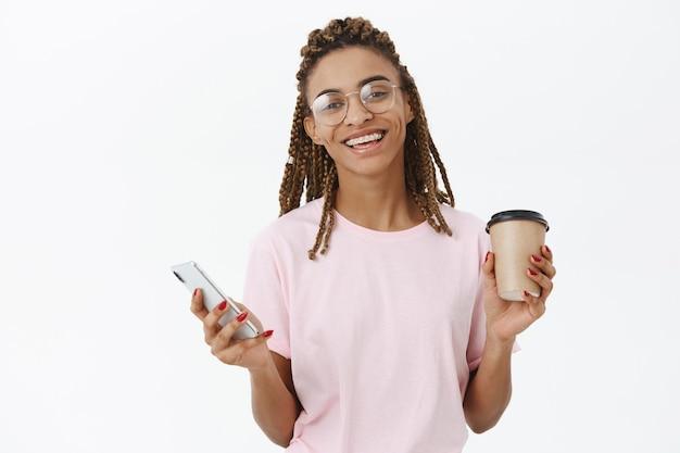 Zachwycona, szczęśliwa i rozbawiona, urocza afroamerykanin dziewczyna z dredami w okularach, trzymając papierowy kubek z kawą i smartfonem