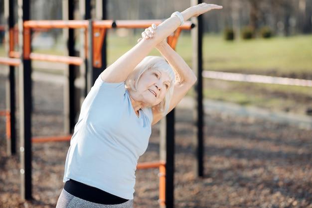 Zachwycona szczupła kobieta uśmiechnięta i ćwicząca na świeżym powietrzu