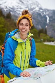 Zachwycona usatysfakcjonowana aktywna dama studiuje mapę