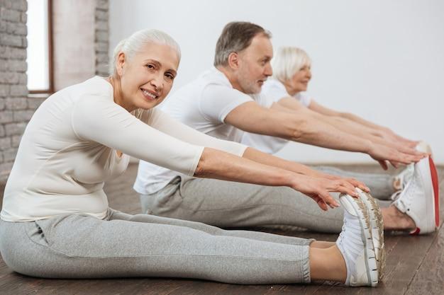 Zachwycona uśmiechnięta starsza kobieta siedzi w półpozycji wyciągając ramiona, patrząc w kamerę