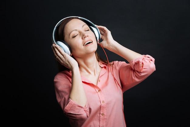 Zachwycona, zainspirowana młoda kobieta czuje się spokojna i używa słuchawek, ciesząc się melodiami i stojąc pod czarną ścianą