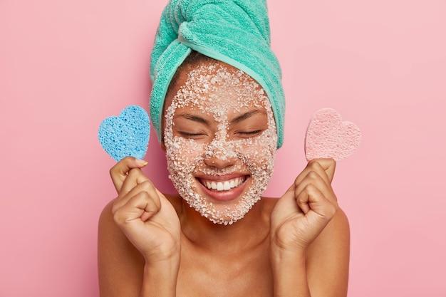 Zachwycona, zdrowa kobieta szczerze się śmieje, ma zamknięte oczy, pokazuje idealne białe zęby, cieszy się wyrazem twarzy, nakłada maskę peelingującą w celu zmniejszenia wyprysków i odświeżenia