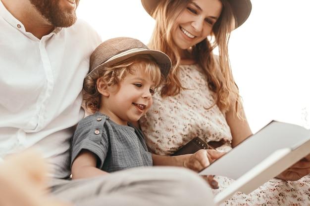 Zachwycony chłopiec czytający bajkę z rodzicami
