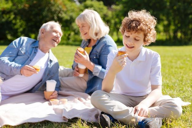 Zachwycony chłopiec, siedząc na trawie, uśmiechając się i patrząc na smakowite ciasto, krzyżując nogi