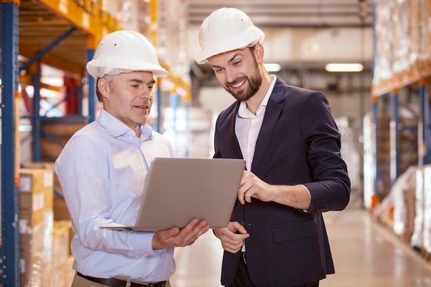 Zachwycony miły mężczyzna wskazując na ekran laptopa, opisując pomysł swojemu menadżerowi